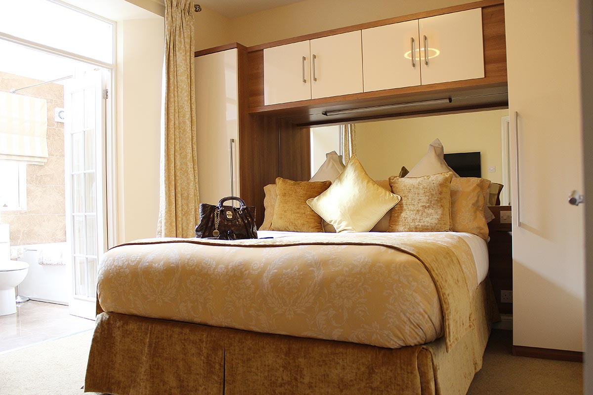 The bedroom in one of our 2 bedroom extended stay apartments leading to an en-suite bathroom