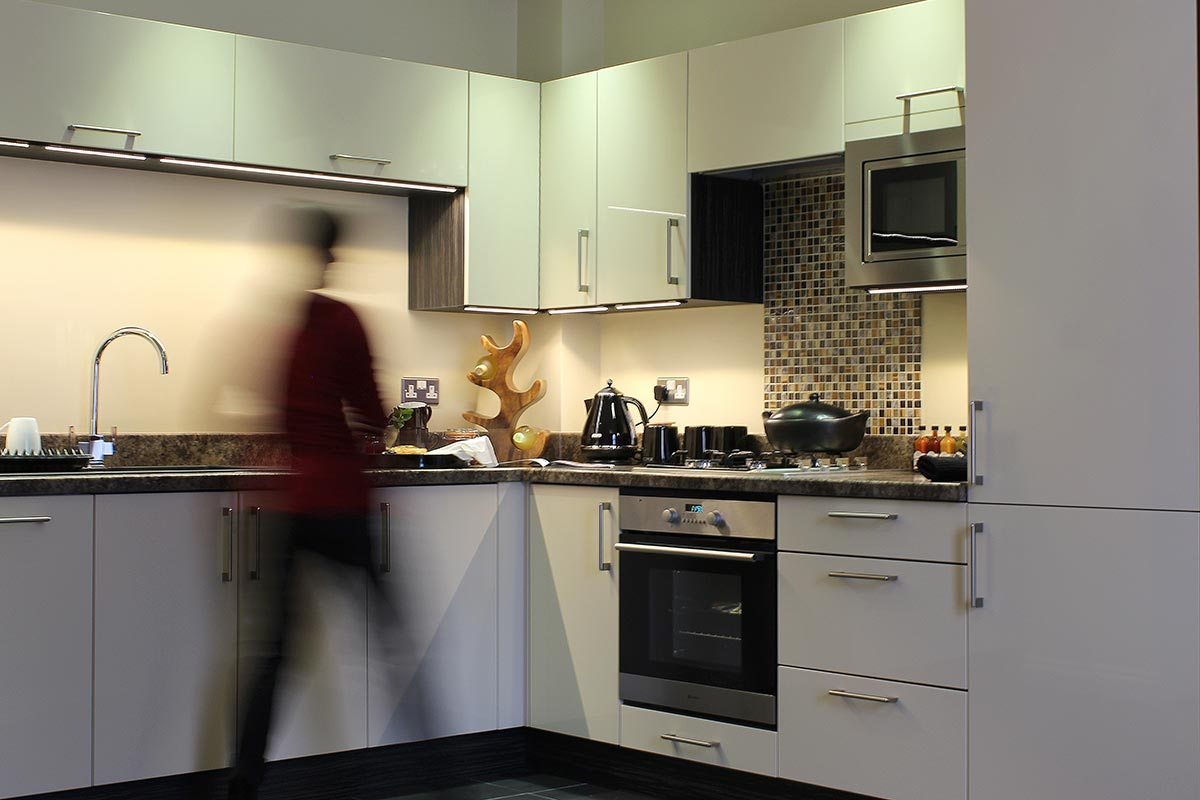 A business guest preparing dinner in one of our self catering, open plan apartments near the corporate hubs of Exeter